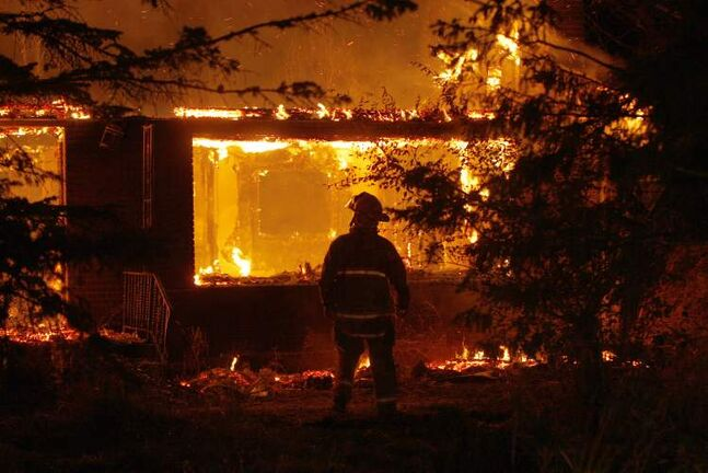 A firefighter watches as fire destroys a vacant house on Highway 15, just outside the city limits, this morning.