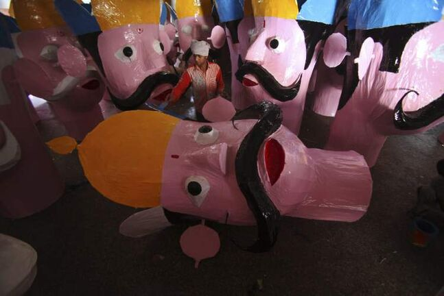 An Indian artist works on the effigies of mythical demon King Ravana in Jammu, India, Friday, Oct. 19, 2012. The effigies will be burned during the upcoming Dussehra festival. Dussehra commemorates the triumph of Lord Rama over the demon king Ravana, marking the victory of good over evil. (AP Photo/Channi Anand)