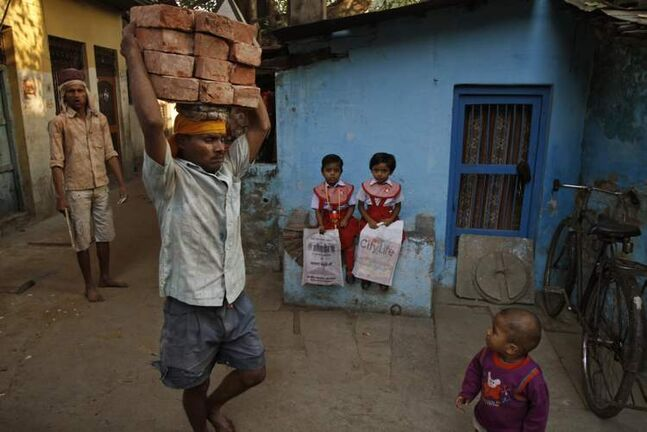An Indian labourer carries bricks on his head as children wait to go to school early in the morning in Allahabad, India, Friday, Oct. 19, 2012. (AP Photo/Rajesh Kumar Singh)