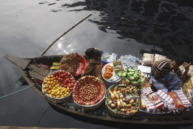 Bangladeshi vendors selling fruits and other items await customers on their boat anchored in the river Buriganga in Dhaka, Bangladesh, Tuesday, Dec. 11, 2012. (AP Photo/Pavel Rahman)