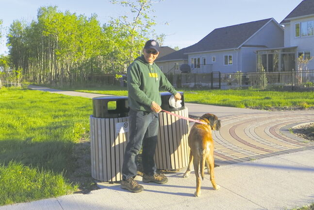 Waverley West resident Ken shows how easy it is to stoop and scoop to get rid of pet waste.
