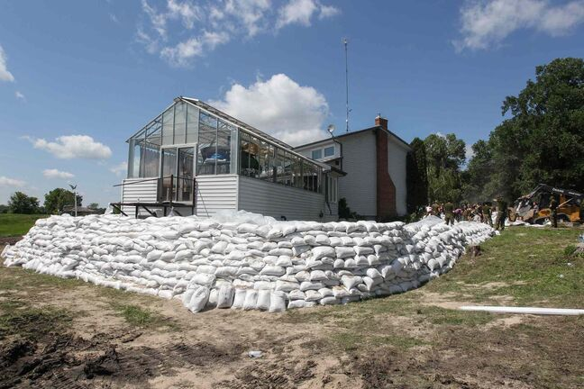 Kevin Van Camp's home with its protective sandbag walls near St. Francois Xavier Sunday afternoon.