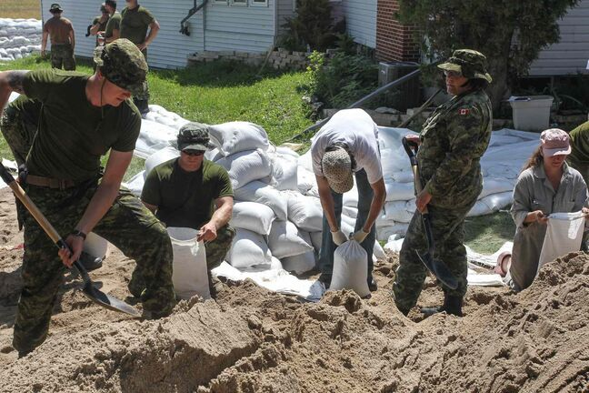 Soldiers from CFB Shilo and volunteers help fortify Kevin Van Camp's home from flood water near St. Francois Xavier Sunday afternoon.