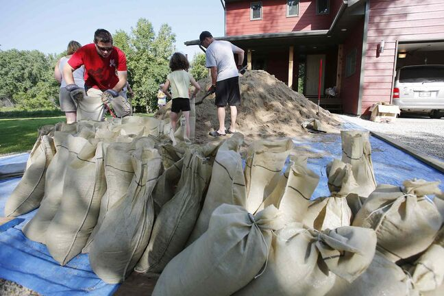 Joerg Zimmermann and his family prepare sandbags at their home in St. Francois Xavier, Man. Saturday. Military reservists have been shipped in to assist with flood preparation from Portage la Prairie to St. Francois Xavier.