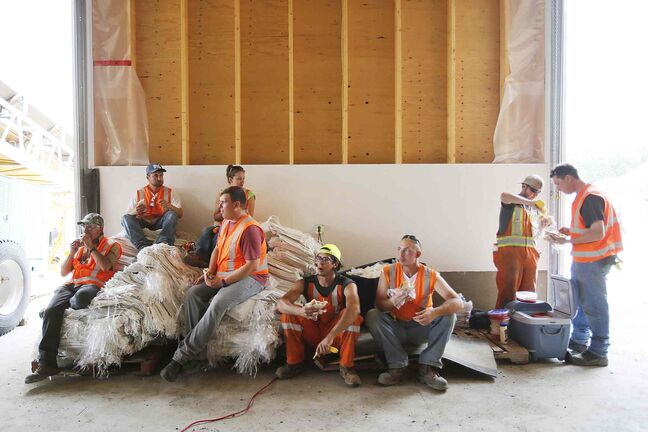 A provincial crew take a break after filling and loading sandbags in 30C temperatures in Portage la Prairie, Man. Saturday.