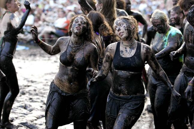 Two women dance in the mud at the Winnipeg Folk Festival on a Sunday evening, July 10, 2005. (BORIS MINKEVICH / WINNIPEG FREE PRESS)