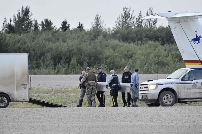 Two metal coffins containing the remains of two manhunt suspects were loaded on two separate RCMP planes at the Gillam airport on Aug. 7, 2019. An autopsy in Winnipeg will confirm their identity and cause of death. (Tessa Vanderhart / Winnipeg Free Press)