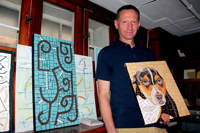 Dimitry Melman poses with one of his mosaic pieces in his studio in the basement of his home.