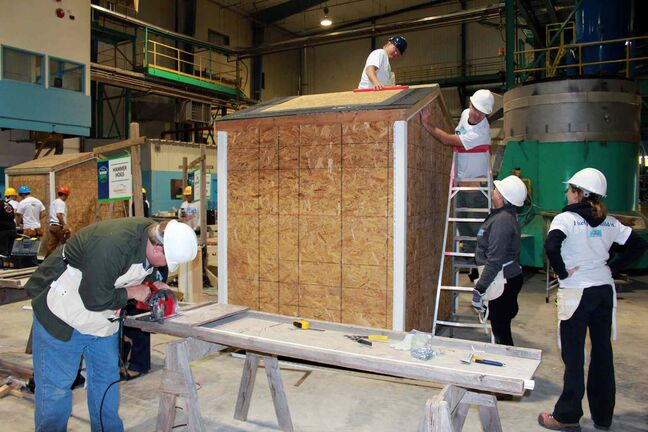 The 'Hammer Hogs' -- a volunteer team from the Manitoba Pork Council -- gets busy building a shed for Habitat For Humanity.