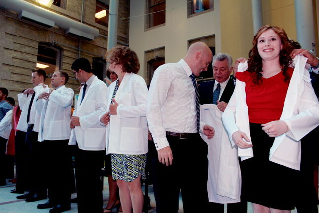 Students were all smiles as they were helped into their white coats Wednesday afternoon in the Brodie Centre atrium at the University of Manitoba's Bannatyne campus.