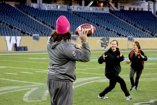 Bombers fullback Michel-Pierre Pontbriand throws a pass to one of the participants in the 2013 Women's Football Clinic.