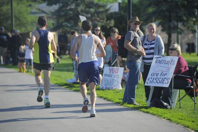 Fans encourage runners with fun signs along the marathon route.