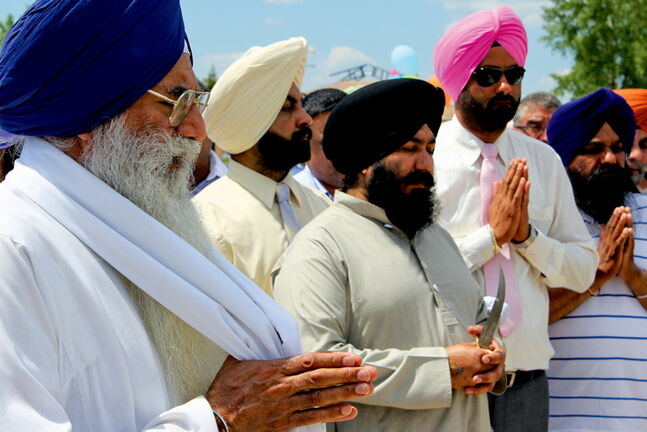 Members of Winnipeg's Sikh community hold a prayer at the site of Waterford Green prior to the development's sod turning last week.