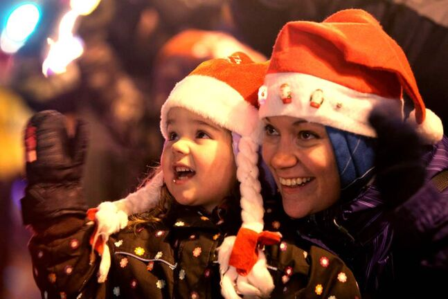 Three-year-old Makaela McMurray and her mom are all smiles as they wave to Santa.