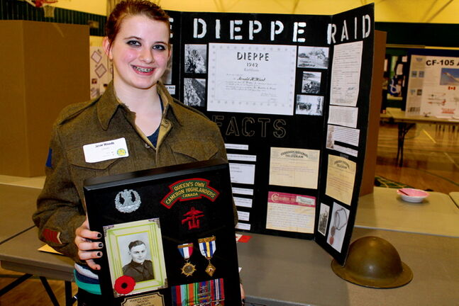 Jessie Wood holds a picture of her great grandfather, Harvey, who fought at Dieppe. The Grade 8 student got the top award for her grade at the St. James Assiniboia School Division Heritage Fair last Thursday.
