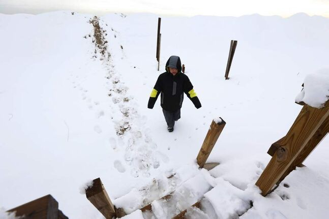 Justin Halstaed, 12, walks down a sand dune covered in snow as wooden planks still standing following Superstorm Sandy stick through the snow at Jenkinson's Boardwalk, Thursday, Nov. 8, 2012, in Point Pleasant, N.J. The New York-New Jersey region woke up to a layer of wet snow and more power outages after a nor'easter pushed back efforts to recover from Superstorm Sandy. (AP Photo/Julio Cortez)