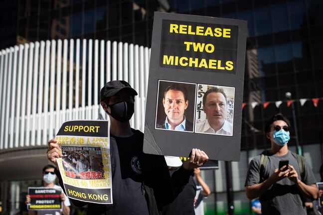 person holds a sign with photographs of Michael Kovrig and Michael Spavor, who have been detained in China since December, 2018, as people gather for a rally in support of Hong Kong democracy, in Vancouver on Aug. 16, 2020.