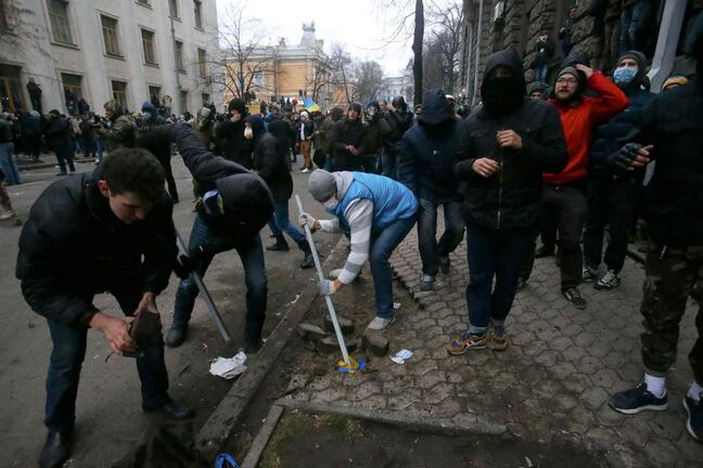 Protesters dig for stones during clashes with police outside the presidential administration building in downtown Kiev, Ukraine, on Sunday. More than 100,000 demonstrators chased away police to rally in the center of Ukraine's capital on Sunday. Thousands of demonstrators tried to storm the nearby presidential administration building, but were driven back by riot police using tear gas and flash grenades, which produce a loud bang but are not intended to cause injury.