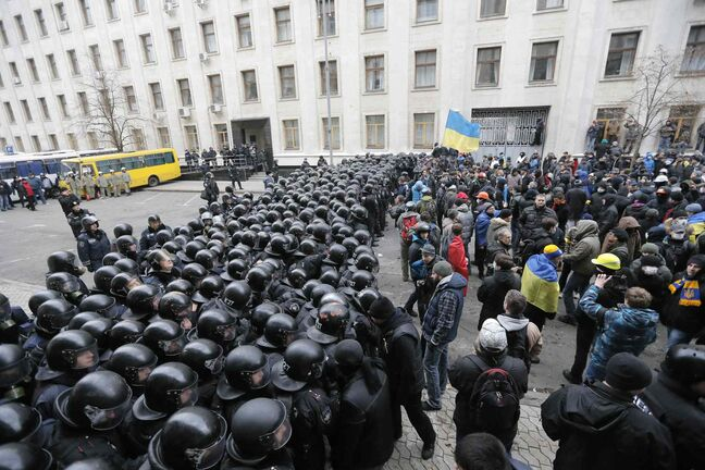 Police block the path of protesters in front of the Presidential office in Kiev, Ukraine, on Sunday. Riot police in Ukraine's capital have used tear gas, truncheons and flash grenades to push back protesters who tried to storm the presidential administration building.