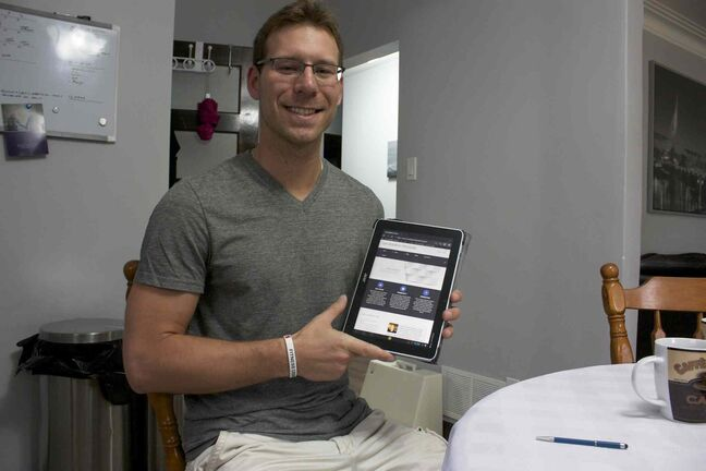 Elmwood Giants defensive co-ordinator Ryan Dueck shows his new website, Six Degrees Freedom, on his tablet.