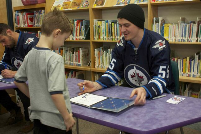 Winnipeg Jets centre Mark Scheifele signs a copy of The Home Team for a young fan at Princess Margaret School on Feb. 25. Scheifele and defenceman Zach Bogosian attended the I Love to Read Month event through the team's Reading Takes Flight program.