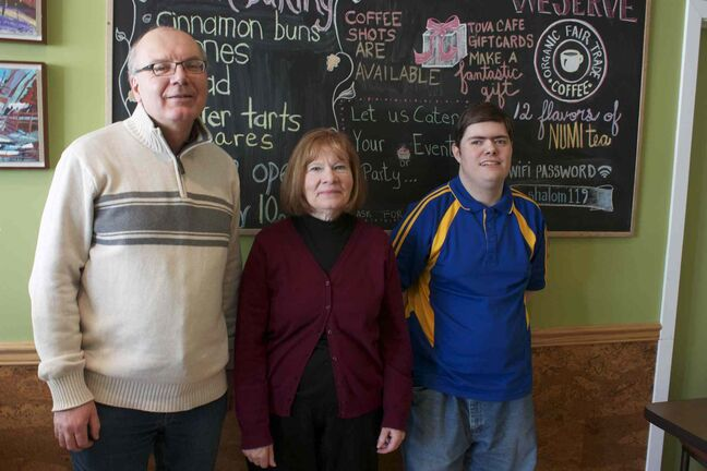 L'Arche executive director Jim Lapp, director of fund development and communications Diane Truderung, and member Leonard, are shown at L'Arche Tova Cafe.