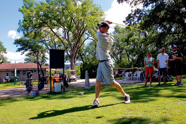 Andrew Littleford tees off with his band (in background) called the Dirty Catfish Brass Band. Windsor Park Golf course in 2012.
