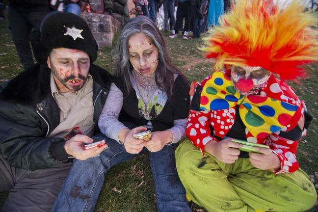(L-R) Alex Ivory, Arielle Morier-Roy, and Danica Audette text prior to the annual Winnipeg Zombie Walk from The Forks to The Manitoba Legislative Building Saturday night. 