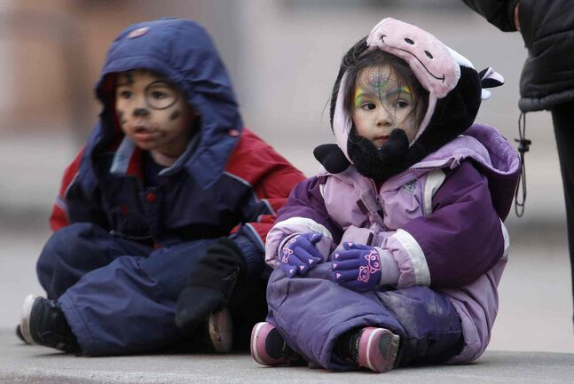 Logan Bancroft, 5, and his sister, Asia, 4, wait for the Santa Claus Parade.