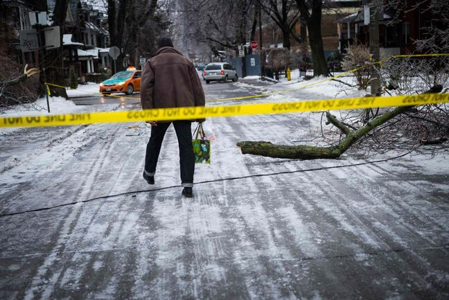 A man steps over downed power lines near Dufferin Grove Park in Toronto on Sunday.