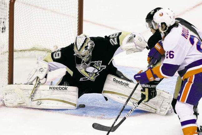 The puck shot by New York Islanders' Kyle Okposo (not seen) slips through the pads of Pittsburgh goalie Marc-Andre Fleury in the third period. The goal, Okposo's first NHL playoff marker, stood as the winner as the Isles rallied to a 4-3 win.