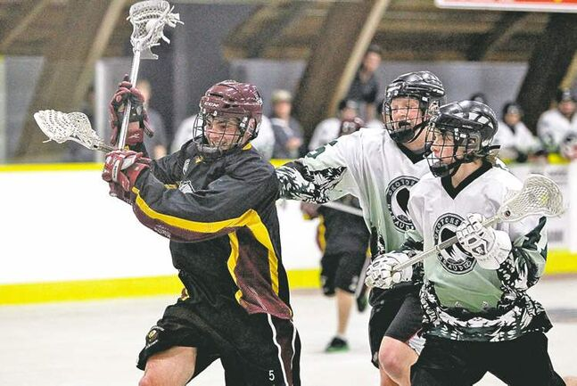 Manitoba's Eli Batt drives for the net with Okotoks Marauders Greyson Smith and Matt McKay (right) in hot pursuit.