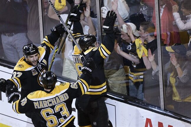 Boston Bruins right wing Reilly Smith (18) celebrates his goal against the Montreal Canadiens with fans during the third period of Game 2 in the second-round of the Stanley Cup hockey playoff series in Boston, Saturday, May 3, 2014. The Bruins won 5-3, tying the best-of-seven games series at one game each. At left are Patrice Bergeron (37) and Brad Marchand (63). (AP Photo/Charles Krupa)