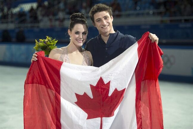Ice dance silver medallists Canada's Tessa Virtue and Scott Moir pose with the Canadian flag during flowers ceremony at the Sochi Winter Olympics Monday, February 17, 2014 in Sochi. THE CANADIAN PRESS/Paul Chiasson