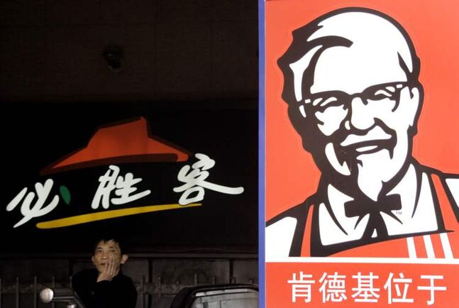 A man stands in front of the signs of KFC and Pizza Hut restaurant  in Shanghai, China.
