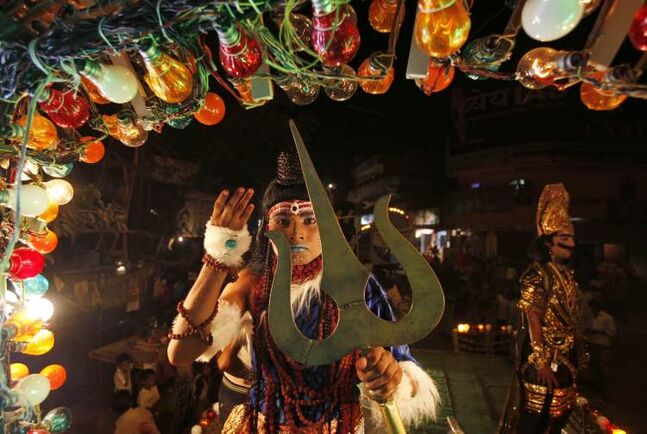 An Indian artist dressed as a Hindu God participates in a Dussehra procession in the northern Indian city of Allahabad, Thursday, Oct. 11, 2012. The procession was part of Hindu festival Dussehra celebrations, commemorating the triumph of Lord Rama over the demon king Ravana, marking the victory of good over evil. (AP Photo/Rajesh Kumar Singh)