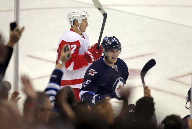 Winnipeg Jets forward Mark Scheifele celebrates teammate Michael Frolik's second-period goal as Detroit Red Wings forward Jordan Tootoo skates by.