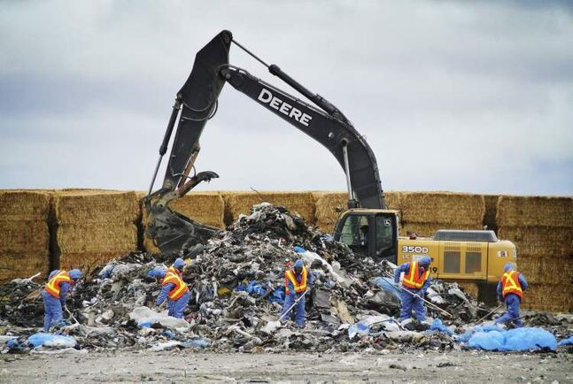 Everything in this photo looks almost purposefully placed. The layers of perfectly-spaced workers, garbage, machines and the hay wall all compliment each other and create an unsettling calm for such a dramatic story.