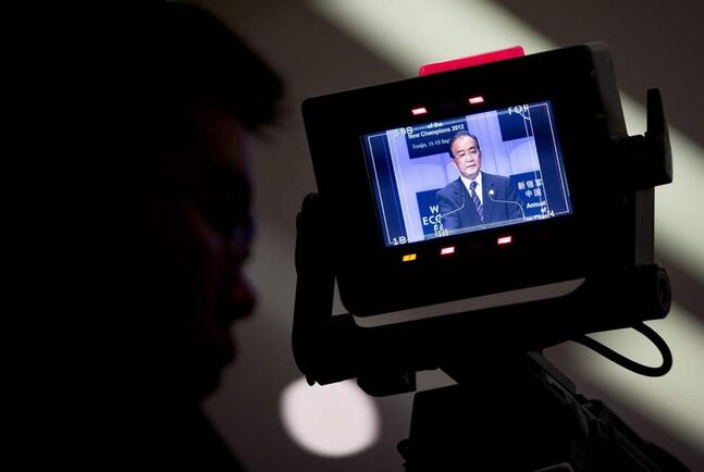 Chinese Premier Wen Jiabao is shown on a television camera's monitor as he delivers his opening speech for the World Economic Forum's 'Annual Meeting of the New Champions' in Tianjin, China. (AP Photo/Andy Wong)