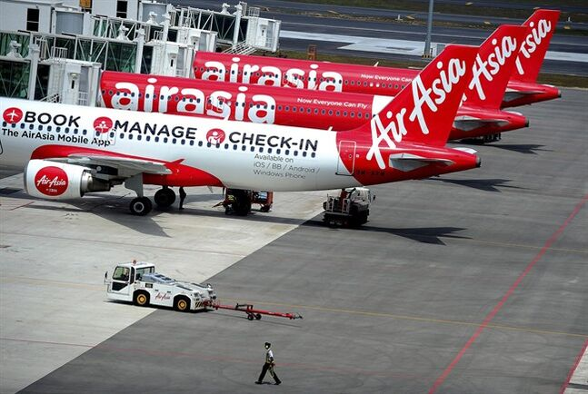 FILE - In this Friday, May 9, 2014 file photo, a ground crewman walks by a fleet of AirAsia's passenger jets on the tarmac of the new low cost terminal KLIA2 in Sepang, Malaysia, as AirAsia began its full operations from the new terminal on the day. The top Asian budget carrier said Tuesday, May 13, it will become the world's first airline to check the passports of all its passengers against Interpol's global database of 42 million stolen or lost travel documents by end of this month. (AP Photo/Joshua Paul, File)