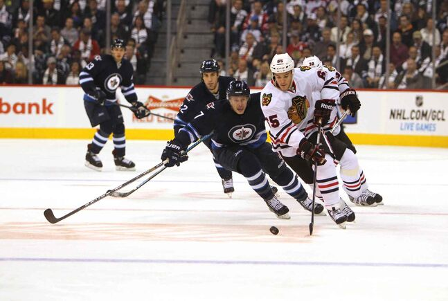 Andrew Shaw (right) of the Blackhawks skates with the puck as James Wright gives chase during the second period.