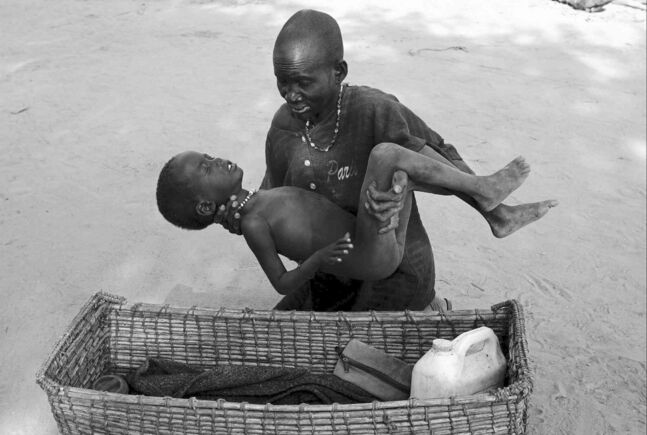 A mother gently places her son in a basket as she takes him to a Médecins Sans Frontières clinic after he contracted malaria, in Lankien, Southern Sudan.