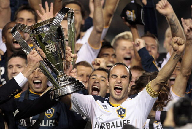 Los Angeles Galaxy forward Landon Donovan holds up the MLS Cup after they won their championship soccer match against the Houston Dynamo in Carson, Calif.