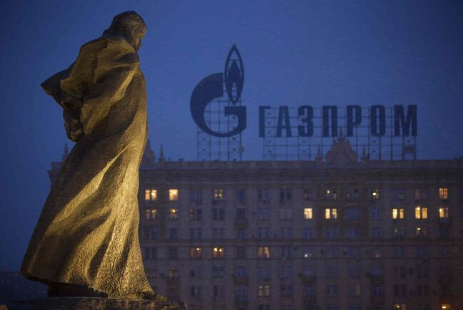 A monument to Ukrainian poet and writer Taras Shevchenko is silhouetted against an apartment building with a sign advertising Russia's natural gas giant Gazprom, in Moscow, Russia, Tuesday, March 4, 2014. Russia's state-controlled natural gas giant Gazprom said Tuesday it will cancel a price discount on gas it sells to Ukraine. Russia had offered the discount in December as part of Russian help for Ukraine. Gazprom also said Ukraine owes it $1.5 billion.