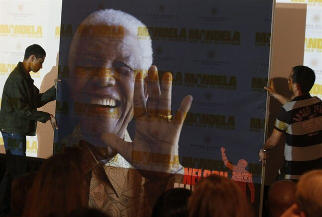 FILE - In this Nov. 2, 2013 file photo, a giant poster of Nelson Mandela is moved to center stage at a news conference held to promote the newly released film