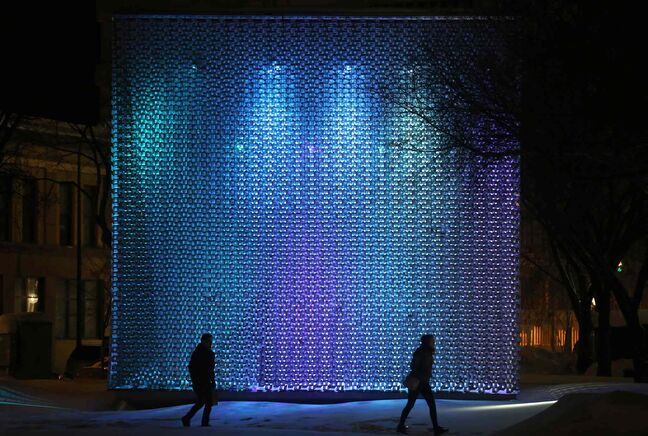 People walk through Old Market Square past The Cube in Winnipeg's Exchange District.
