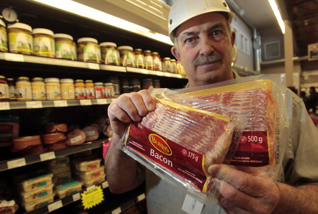 Butcher Gilbert Kohlman of Cantor's Grocery Co. holds two packages of bacon weighing 500 grams and 375 grams. Both cost the same. Bacon producers are reducing the weight of standard packages.