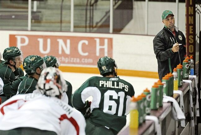 ADVANCE FOR WEEKEND EDITIONS, SEPT. 14-15 - Minnesota Wild head coach Mike Yeo, right, works with his team during the first day of NHL hockey training camp at Ridder Arena on the University of Minnesota Campus, Thursday, Sept. 12, 2013 in Minneapolis. They needed to win their last regular-season game to qualify for the playoffs, after creating a pre-lockout buzz by signing stars Zach Parise and Ryan Suter. Yeo kept his job, but another eighth-place finish won't cut it for this club.(AP Photo/Craig Lassig)