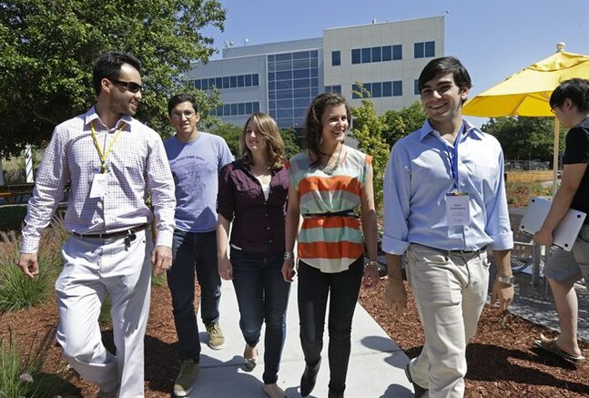 Google interns, from left, Steve Weddler, Alfredo Salinas, Lizzy Burl, Rita DeRaedt, and Alex Rodrigues walk on the Google campus, Wednesday, May 21, 2014, in Mountain View, Calif. With summer's arrival comes an influx of thousands of Silicon Valley interns, and these kids aren't just fetching coffee. Well paid and perked, young up-and-comers from around the world who successfully navigate the competitive application process are assigned big time responsibility at firms like Google, Facebook, Drop Box and Twitter, where executives hope that a fun and stimulating summer will motivate them to come back after graduation to launch careers. (AP Photo/Ben Margot)