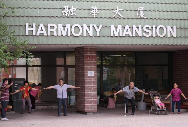 People do early morning exercises outside the Harmony Mansion building on Princess Street Thursday morning.